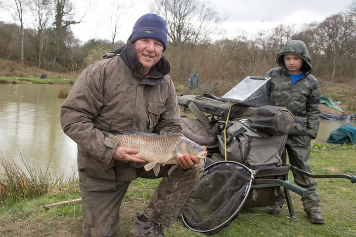 Steve with his match winning carp as Cody looks on